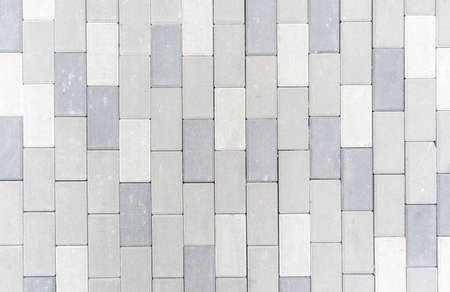 Concrete or paved newly laid gray paving slabs or stones for floors or walkways. Concrete paving slabs in the backyard or road paving. Garden brick path in the courtyard on a sandy foundation Stockfoto
