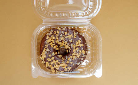 Chocolate donut in a plastic container on a brown or coffee background. Takeaway breakfast concept. One donut is packed in a plastic box for delivery. Sweet pastries delivered to your home. Top view