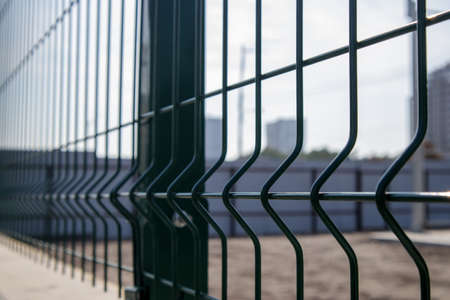 Steel lattice green fence with wire. Fencing. Grid industrial wire fence panels, pvc metal. Installation of sectional fencing. Welded mesh fence. Installation of a grid for fencing the territory