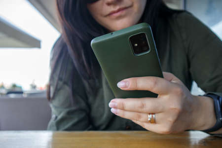 Close up of woman's hand with wedding ring holding cell or mobile phone during coffee break. A woman in a green dress is reading something on her smartphone while sitting in a modern cafe Stockfoto