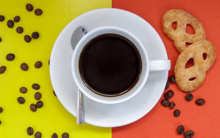 Black coffee in a white coffee cup on a bright background. Top view, flat lay, copy space. Cafe and bar, barista art concept. Freshly made natural or instant coffee in a cup. Coffee background