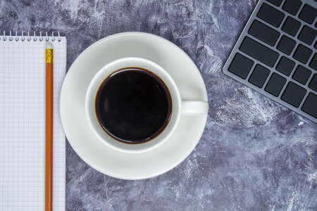 Workspace with keyboard, stationery, pencil, notepad and coffee cup on gray table. Flat lay, office table top view. The concept of business financing and freelancing remote work. Copy space