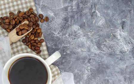White cup of black coffee americano, cloth shawl with coffee beans scattered on a gray table. Beautiful cup composition. Flat lay, top view, copy space. Relaxation concept