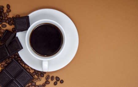 Black American coffee without milk in a white cup, chocolate and coffee beans. Top view, flat lay, place for text. A cup of aromatic morning coffee. Nice background for cafe, restaurant menu Stockfoto