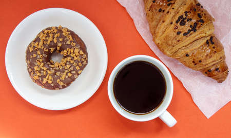 One chocolate donut, croissant and black Americano coffee without milk in a white cup on a bright background. Top view, flat lay. Freshly brewed or instant hot coffee drink with sweet pastries Stockfoto