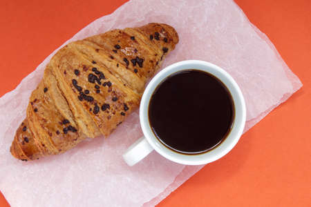 Black coffee without milk in a white cup and a chocolate croissant on parchment and bright background. French breakfast with fresh pastries. Top view flat with copy space for your text