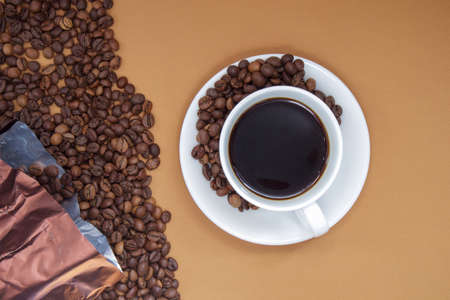 White cup of Americano black coffee without milk with a bunch of roasted coffee beans scattered from paper packaging. Coffee background, top view with copy space
