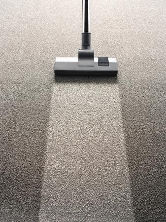 servicio domestico: Aspirador en una alfombra con una tira limpia extra para espacio de la copia