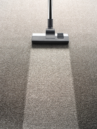 dirty room: Vacuum cleaner on a carpet with an extra clean strip for copy space