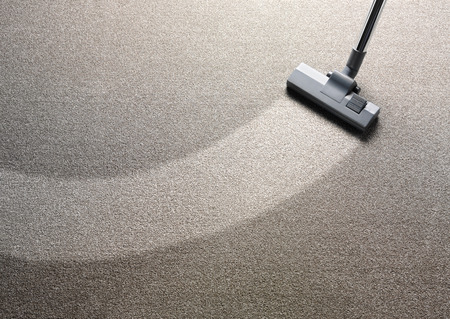 dirty carpet: Vacuum cleaner on a carpet with an extra clean strip for copy space