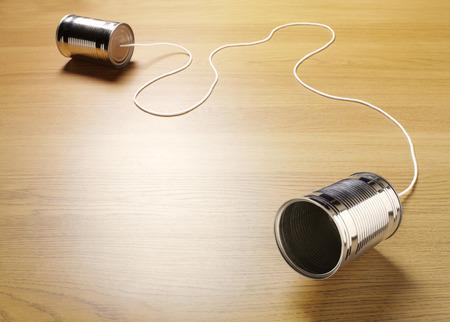 通信: 原始的なコミュニケーションのための木製の背景のコードで結合されている 2 つのブリキ缶