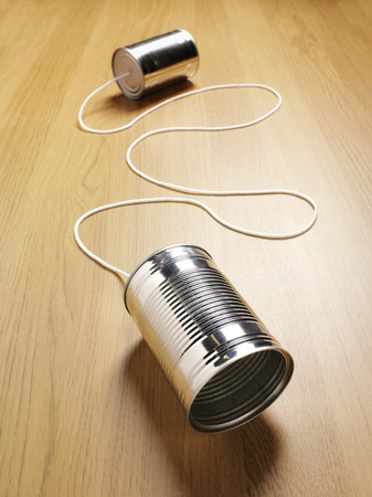 Two tin cans joined with a cord on a wooden background with copy space for primitive communication.
