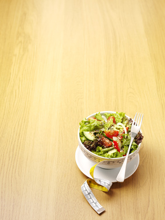 A bowl of mixed salad with a tape measure for healthy eating on a wooden background with copy space Stock Photo