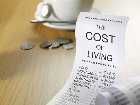 printout: Cost of living figures on a paper printout with American cents on a table.