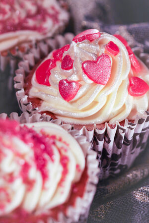 piped: Cupcake with swirl icing and sugar hearts