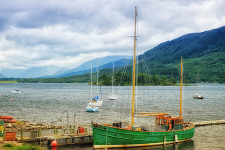 british weather: Green ship floating at the loch shore