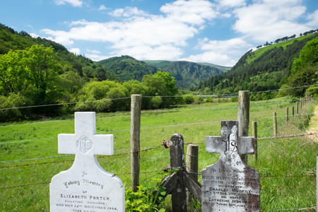 gravestones: Historic gravestones and a view of the valley at Glendalough, Ireland