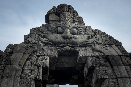 Archway with a carved face at Borobudur temple photo