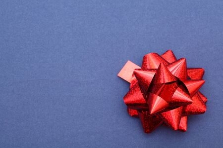 red ribbon bow: Red bow on blue paper background. Closeup.