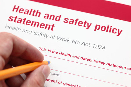 safety: Health and safety policy statement and hand with ballpoint pen. Stock Photo