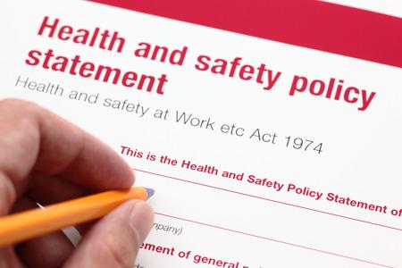 Zdraví a bezpečnost politika prohlášení a ruku s kuličkovým perem.
