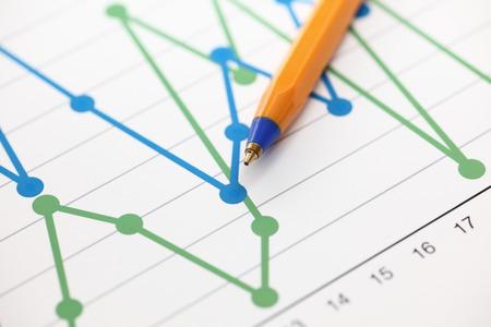 財務諸表 (折れ線グラフ) の分析。ビジネス グラフ、ボールペン。クローズ アップ。 写真素材