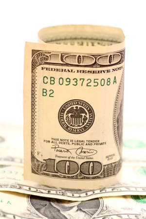 one hundred dollar bill: Roll of One Hundred Dollar Bill on one dollar bill heap against white background. Close-up.