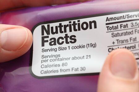 Het lezen van een voedingswaarde feiten over cookies verpakking. Detailopname. Stockfoto