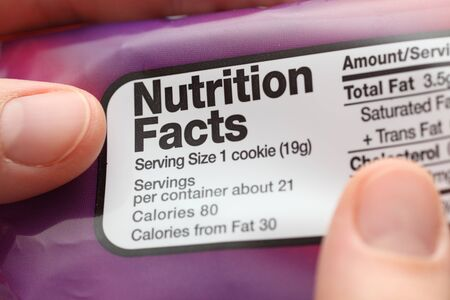 Reading a nutritional facts on cookies packaging. Close-up.