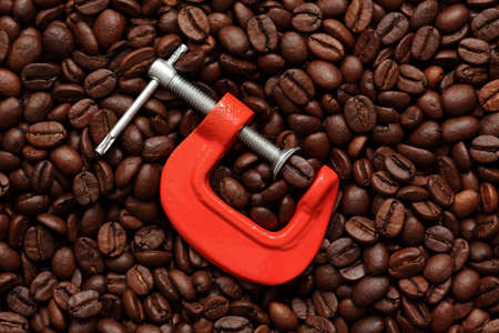 vise grip: Coffee bean in a clamp on coffee beans background. Close-up. Stock Photo