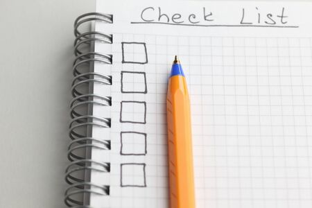 Checklist with ballpoint pen. Close-up.