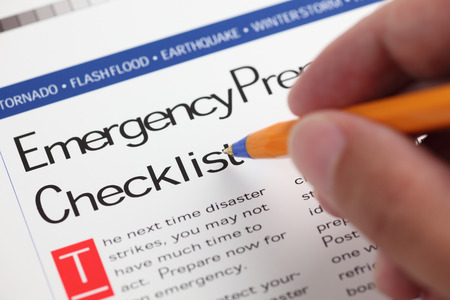 Emergency Checklist and hand with ballpoint pen. Close-up.