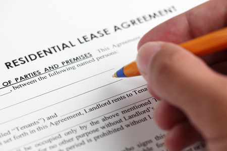 Residential lease agreement and human hand with ballpoint pen. Close-up.