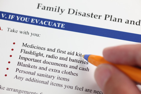 disaster: Family Disaster Plan and hand with ballpoint pen. Close-up.