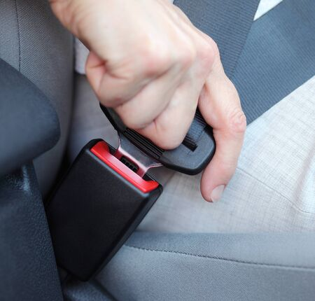 safety belt: Person fastening safety belt in car.
