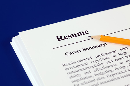 Stack of resumes with pencil on a blue . Stock Photo
