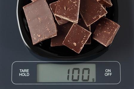 black gram: Broken dark chocolate in a black plate on digital scale displaying 100 gram.