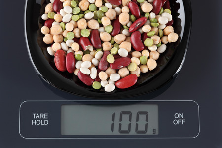 black gram: Mixed legume beans in a black plate on digital scale displaying 100 gram. Stock Photo