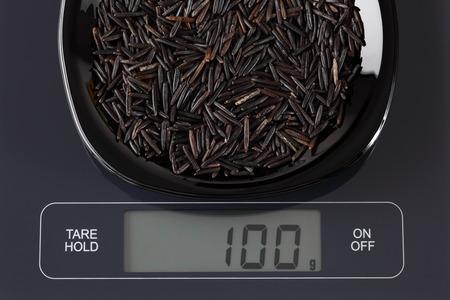 black gram: Wild rice in a black plate on digital scale displaying 100 gram.