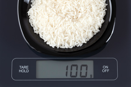 black gram: White rice in a black plate on digital scale displaying 100 gram. Stock Photo