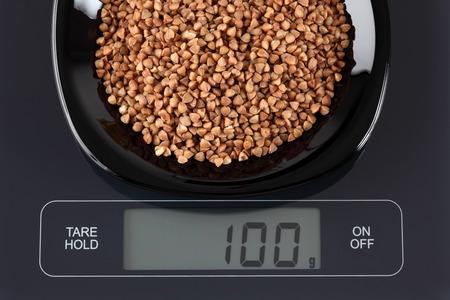 black gram: Buckwheat in a black plate on digital scale displaying 100 gram. Stock Photo