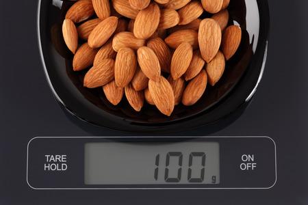 black gram: Almonds in a black plate on digital scale displaying 100 gram.
