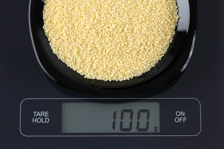 black gram: Couscous in a black plate on digital scale displaying 100 gram.
