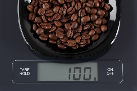 black gram: Coffee beans in a black plate on digital scale displaying 100 gram. Stock Photo