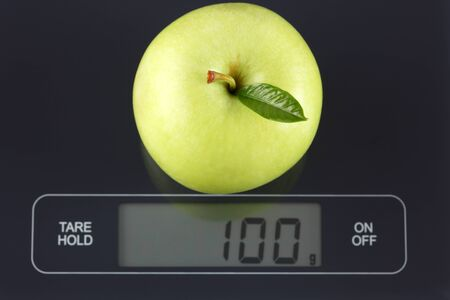 gram: Green apple on digital scale displaying 100 gram.