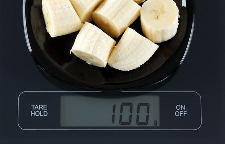black gram: Peeled sliced ??banana in a black plate on digital scale displaying 100 gram. Stock Photo