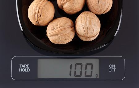 black gram: Walnuts in a black plate on digital scale displaying 100 gram. Stock Photo