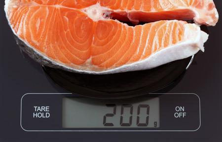 escamas de peces: Steak de salm�n pescado en un plato negro sobre balanza digital que muestra de 200 gramos.
