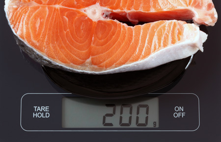 Steak of salmon fish in a black plate on digital scale displaying 200 gram.
