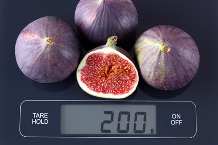 gram: Three and half fresh figs on digital scale displaying 200 gram. Stock Photo
